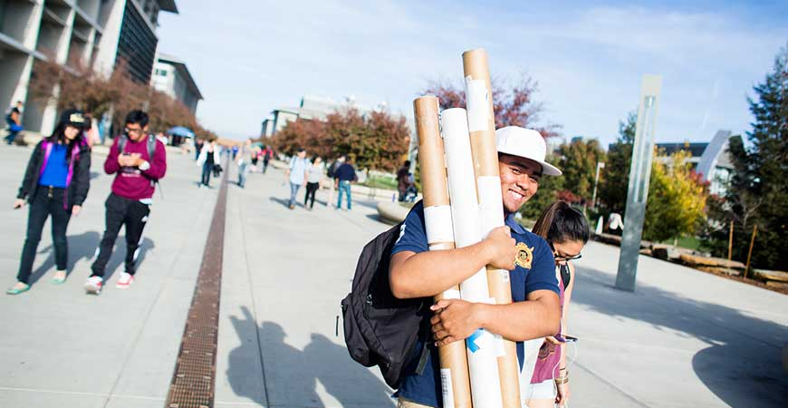 A smiling male student walks along Scholars Lane while carrying an arm full of papers.