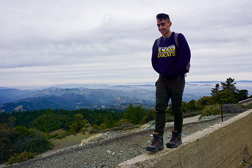 Adrian Buitron Boada, a student in the Leadership & Service Living Learning Community, walks along a wall atop Mount Tamalpais.