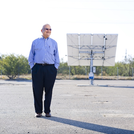 A man in a blue shirt and black pants stands in front of a solar panel.