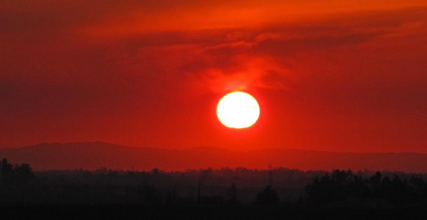 Sun setting in red-orange sky over darkened mountain range as seen from UC Merced's Kolligian Library.