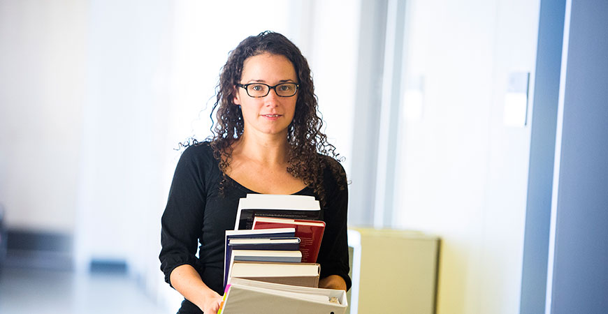 Woman with dark curly hair and glasses carrying a stack of books