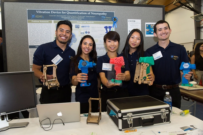 Five college student hold up electronic components they've invented