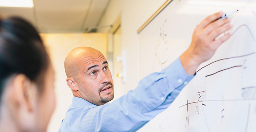 Professor Nathan Monroe works with a student to analyze politics.
