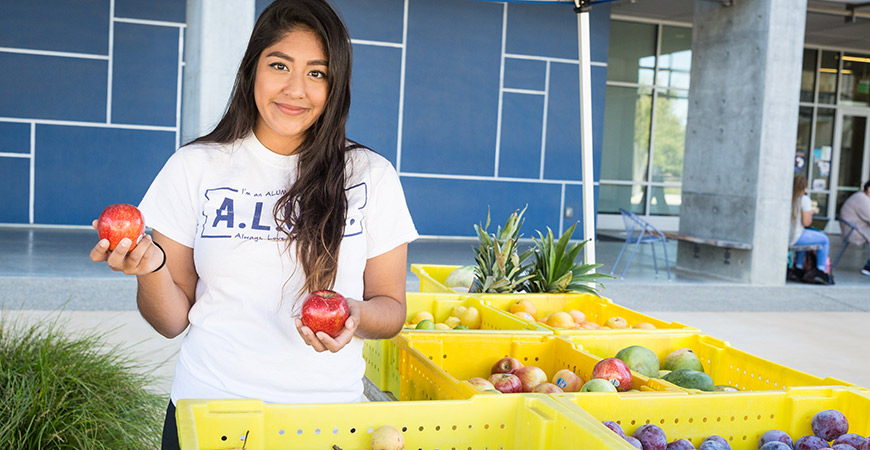 Student behind a produce stand