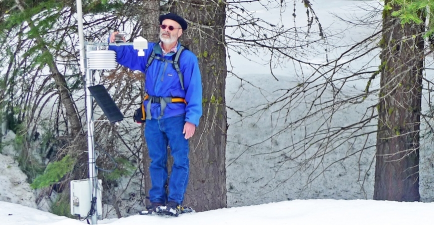 A man in a blue jacket, blue jeans and sunglasses stands in a snowy forest repairing an electronic sensor device.