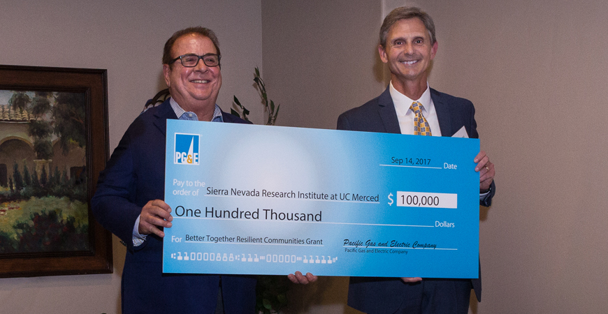 Two men pose with an oversized check on stage at a check presentation ceremony for the PG&E award to SNRI.