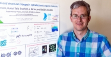 Professor Strubbe stands in front of a research poster.